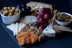 Τυρί, κροτίδες, σταφύλι, καρύδια σε ένα μαύρο υπόβαθρο Στοκ φωτογραφία με δικαίωμα ελεύθερης χρήσης