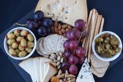 Τυρί, κροτίδες, σταφύλι, καρύδια σε ένα μαύρο υπόβαθρο Στοκ φωτογραφίες με δικαίωμα ελεύθερης χρήσης