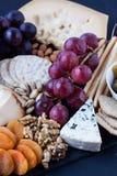 Τυρί, κροτίδες, σταφύλι, καρύδια σε ένα μαύρο υπόβαθρο Στοκ Εικόνες