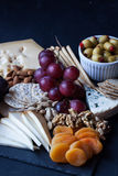 Τυρί, κροτίδες, σταφύλι, καρύδια σε ένα μαύρο υπόβαθρο Στοκ εικόνα με δικαίωμα ελεύθερης χρήσης