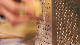 Τυρί μοτσαρελών που περνά μέσω του ξύστη που πυροβολείται ενός κομματιού του τυριού φιλμ μικρού μήκους
