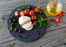 Τυρί μοτσαρελών με τις ντομάτες κερασιών, το arugula και τις μαύρες ελιές Στοκ φωτογραφίες με δικαίωμα ελεύθερης χρήσης