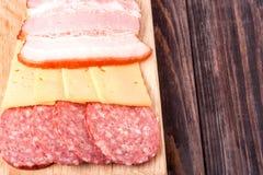 Τυρί, μπέϊκον και σαλάμι σε έναν τέμνοντα πίνακα Στοκ εικόνα με δικαίωμα ελεύθερης χρήσης
