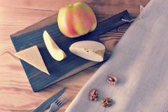 Τυρί παρμεζάνας και η Apple στην επιτροπή και τα ξεφλουδισμένα ξύλα καρυδιάς Στοκ Εικόνα