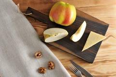 Τυρί παρμεζάνας και η Apple στην επιτροπή και τα ξεφλουδισμένα ξύλα καρυδιάς Στοκ εικόνα με δικαίωμα ελεύθερης χρήσης