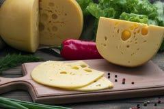 Τυρί που τεμαχίζονται και ολόκληρα, φρέσκα χορτάρια και πιπέρι Στοκ Φωτογραφίες