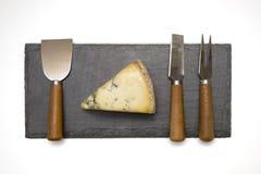 Τυρί στον πίνακα πλακών με τα μαχαιροπήρουνα Στοκ Εικόνα
