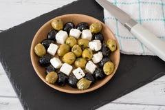 Τυρί φέτας με τις πράσινες και μαύρες ελιές που εξυπηρετούνται σε ένα κύπελλο στοκ εικόνες