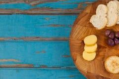 Τυρί, ψωμί, ελιές και μπισκότα στον ξύλινο πίνακα Στοκ Εικόνες