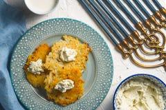 Τυρί Latkes και στάρπης σε ένα πιάτο και σε μια μπλε πετσέτα, chanukia Στοκ Φωτογραφίες