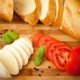 Τυρί Mozarella με τις φρέσκα ντομάτες και το baguette Στοκ Φωτογραφίες