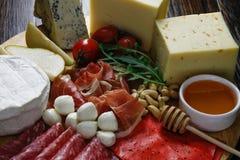 Τυρί Platte με τα διαφορετικά τυριά, κρέατα στον ξύλινο πίνακα Στοκ Φωτογραφία