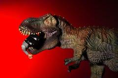 Τυραννόσαυρος που δαγκώνει έναν μικρό δεινόσαυρο με το φως σημείων στο κεφάλι και το κόκκινο φως Στοκ φωτογραφία με δικαίωμα ελεύθερης χρήσης
