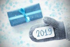 Τυρκουάζ δώρο, γκρίζο γάντι δεράτων, κείμενο 2019, Snowflakes στοκ φωτογραφία με δικαίωμα ελεύθερης χρήσης