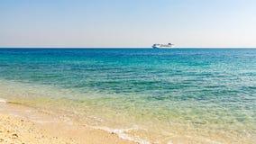 Τυρκουάζ θάλασσα με τους ελαφριούς κυματισμούς στο νερό και ένα μεγάλο σκάφος της γραμμής κρουαζιέρας στον ορίζοντα στοκ εικόνες με δικαίωμα ελεύθερης χρήσης