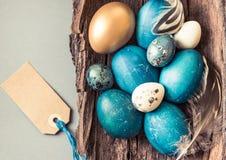 Τυρκουάζ και χρυσός αυγών Πάσχας στο αγροτικό ξύλινο διάστημα κειμένων υποβάθρου Κάρτα διακοπών Πάσχας Στοκ Φωτογραφίες