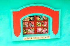 Τυρκουάζ & κόκκινο πλαίσιο παραθύρων με τα floral πλακάκια στο Μεξικό στοκ φωτογραφία