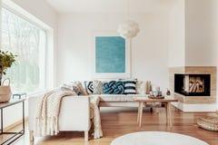 Τυρκουάζ μπλε μαξιλάρι κόμβων σε έναν μπεζ καναπέ γωνιών και μια αφηρημένη αφίσα σε έναν άσπρο τοίχο σε ένα σύγχρονο εσωτερικό κα στοκ φωτογραφία