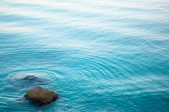 Τυρκουάζ υπόβαθρο θάλασσας και παράκτιες πέτρες στοκ εικόνες με δικαίωμα ελεύθερης χρήσης