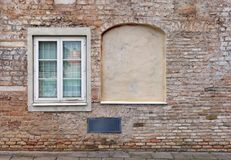 Τυφλά κυρτά παράθυρα υπογείων στο παλαιό ηλικίας κόκκινο σπίτι τούβλων στοκ φωτογραφία