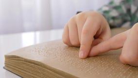 Τυφλά χέρια παιδιών που διαβάζουν το βιβλίο μπράιγ με την πηγή συμβόλων για τη με οπτική αναπηρία στενή επάνω συνεδρίαση στον πίν απόθεμα βίντεο