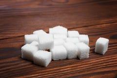 Τυχαίος σωρός των γλυκών κύβων ζάχαρης σε έναν σκοτεινό καφετή ξύλινο πίνακα Καθαρισμένη άσπρη ζάχαρη στον πίνακα Λίγα κομμάτια τ Στοκ Εικόνες