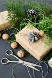 Τυλίγοντας τις αγροτικές συσκευασίες Χριστουγέννων eco με το καφετί έγγραφο, η σειρά και το φυσικό έλατο διακλαδίζονται στο σκοτε Στοκ φωτογραφία με δικαίωμα ελεύθερης χρήσης