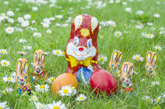 Τυλιγμένα λαγουδάκια σοκολάτας με τα αυγά Πάσχας στη χλόη Στοκ εικόνες με δικαίωμα ελεύθερης χρήσης