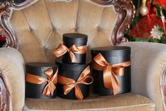 Τυλιγμένα μαύρα κουτιά δώρων με τις κορδέλλες ως χριστουγεννιάτικα δώρα σε μια καρέκλα Στοκ φωτογραφία με δικαίωμα ελεύθερης χρήσης