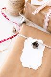 Τυλιγμένα δώρα που διακοσμούνται με τα ασημένιες κουδούνια και τις ετικέττες δώρων Στοκ Εικόνα