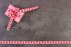 Τυλιγμένο δώρο με την κορδέλλα για την ημέρα βαλεντίνων, διάστημα αντιγράφων για το κείμενο Στοκ Εικόνες