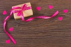 Τυλιγμένο δώρο με την κορδέλλα και καρδιές για την ημέρα βαλεντίνων, διάστημα αντιγράφων για το κείμενο Στοκ Φωτογραφίες