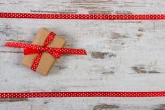 Τυλιγμένο δώρο με την κόκκινη κορδέλλα για την ημέρα βαλεντίνων, διάστημα αντιγράφων για το κείμενο Στοκ φωτογραφία με δικαίωμα ελεύθερης χρήσης