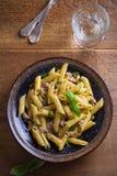 Τόνος, βασιλικός και κάπαρη penne με τη σάλτσα pesto στο κύπελλο στο ξύλινο υπόβαθρο Ζυμαρικά με τα ψάρια τόνου στοκ φωτογραφία με δικαίωμα ελεύθερης χρήσης