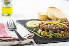 Τόνος τόννων tartare σε ένα μαύρο πιάτο πλακών με το αβοκάντο Στοκ εικόνες με δικαίωμα ελεύθερης χρήσης