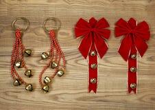 Τόξα και κουδούνια Χριστουγέννων στο ηλικίας ξύλο Στοκ Εικόνες