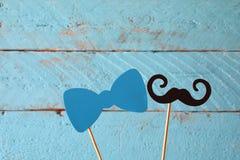 Τόξο εγγράφου και mustache στα ραβδιά μπροστά από το ξύλινο υπόβαθρο Στοκ Εικόνα