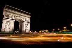 Τόξο de triomphe τη νύχτα με τα ίχνη κυκλοφορίας Στοκ Φωτογραφίες