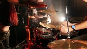 Τύμπανα παιχνιδιού νεαρών άνδρων σε μια ορχήστρα ροκ απόθεμα βίντεο