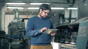 Τύποι ατόμων σε μια ταμπλέτα ελέγχοντας τις τυπογραφικές μηχανές απόθεμα βίντεο