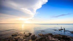 Τύποι με τη στάση ράβδων στις πέτρες στη θάλασσα στο ηλιοβασίλεμα στα ψάρια απόθεμα βίντεο