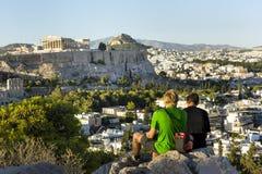 2 τύποι που κάθονται σε έναν λόφο απέναντι από την ακρόπολη στην Αθήνα, άποψη στοκ εικόνα