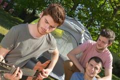 Τύποι που παίζουν την κιθάρα στο campground στη φύση στοκ εικόνα με δικαίωμα ελεύθερης χρήσης
