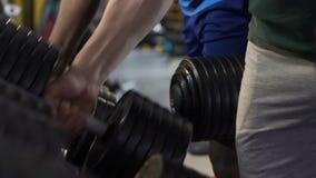 Τύποι που παίρνουν και που ξαναβάζουν τους βαριούς αλτήρες για να σταθεί στη γυμναστική, κατάρτιση μυών φιλμ μικρού μήκους