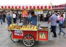 Τύποι που πωλούν τα ψημένα κάστανα και τα δημητριακά σε Eminonu στοκ εικόνες