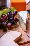 3 τύποι τυριών, ακόμα Roquefort ζωής, τυρί Cheddar, κάπνισαν το τυρί και το κόκκινο και πράσινο ξύλο καρυδιάς σταφυλιών Στοκ Εικόνες