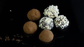 Τύπος δύο καραμελών σοκολάτας που εξυπηρετούνται στο μαύρο υπόβαθρο απόθεμα βίντεο