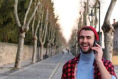 Τύπος ισχίων που μιλά στο κινητό τηλέφωνο υπαίθρια Στοκ Εικόνες