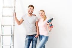 Τύπος και κορίτσι που στέκονται κοντά στον άσπρο τοίχο δίπλα στη σκάλα Στοκ Φωτογραφία