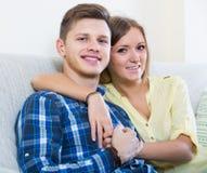 Τύπος και όμορφη αγκαλιά κοριτσιών στον καναπέ στο εσωτερικό Στοκ Εικόνες